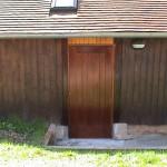 Porte de service en bois exotique. Ouverture sur l'extérieure avec barre anti-panique.